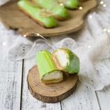 Eclair cut with tangerine jelly, orange mousse and mascarpone cream decorated with green icing and gold lace decoration. On wooden plate. The concept of royalty free stock photo