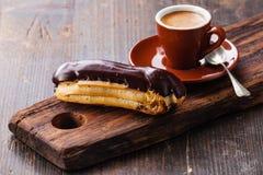 Eclair de chocolate y taza de café Imagen de archivo