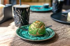 Eclair del pistacho, profiterole en esmalte en la placa verde en la tabla, cierre para arriba Eclair, tarta de las natillas con c fotografía de archivo libre de regalías