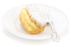 Eclair dessert powdered sugar. Eclair with powdered sugar filled custard on a white plate with an elegant fork Stock Photography