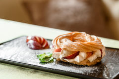 Eclair donut desert  breakfast,  on black plate and green tablecloth at morning Stock Photography