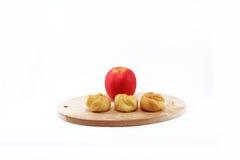 Eclair e maçã vermelha na placa de madeira do corte; Fundo branco Fotos de Stock