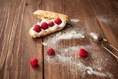 Eclair with fresh raspberries on wood table, confectioner table Stock Photography