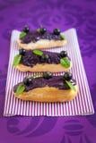 Eclair med kräm- och svarta vinbär Royaltyfri Foto