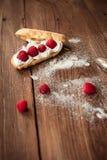 Eclair poner crema con las frambuesas frescas en la tabla de madera Imágenes de archivo libres de regalías