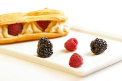 Eclair with raspberries & bilberries Stock Photo