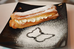 Eclair. With vanilla cream and almond cream royalty free stock photography