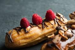 Eclairs με τα φυστίκια, την τήξη σοκολάτας και τα σμέουρα Στοκ εικόνα με δικαίωμα ελεύθερης χρήσης
