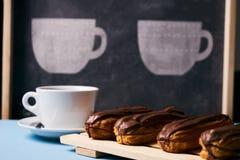 eclairs и чашка чаю Стоковые Изображения RF