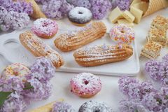 Eclairs и donuts с кофе с сиренью цветут, на мраморной предпосылке, светлая предпосылка, кондитерская в стиле блоггера Стоковые Фото