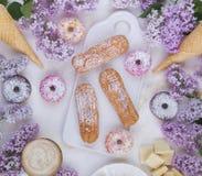 Eclairs и donuts с кофе с сиренью цветут, на мраморной предпосылке, светлая предпосылка, кондитерская в стиле блоггера Стоковое Изображение RF