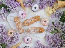 Eclairs и donuts с кофе с сиренью цветут, на мраморной предпосылке, светлая предпосылка, кондитерская в стиле блоггера Стоковое Фото