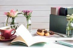 Eclairs на белом деревянном столе с чашкой кофе, цветками весны и открытой тетрадью с чернилами рисуют Стоковые Изображения