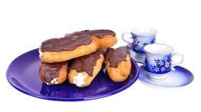 Eclairs на голубой плите с чашками coffe Стоковое Изображение