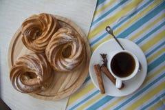 Eclairs на деревянных плите и чашке эспрессо Стоковое Изображение RF