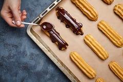 Eclairs при шоколад и взбитая сливк подготавливая на листе выпечки Стоковые Изображения RF