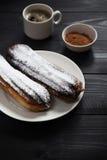 Eclairs сахара и чашка кофе Стоковое Фото