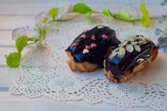 2 eclairs шоколада кладут на seviette около зеленого стержня цветка на деревянном столе Стоковые Фото