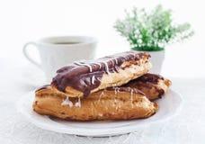 Eclairs шоколада на белой плите Стоковое фото RF