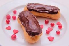 Eclairs шоколада на плите на белой предпосылке взбрызнутой с ягодами и сердцами красной смородины Стоковое Фото