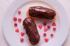 Eclairs шоколада на плите на белой предпосылке взбрызнутой с ягодами и сердцами красной смородины Стоковые Изображения