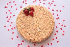 Eclairs шоколада на плите на белой предпосылке взбрызнутой с ягодами и сердцами красной смородины Стоковая Фотография RF
