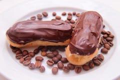 Eclairs шоколада на плите на белой предпосылке Стоковые Фото