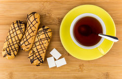 Eclairs, black tea in cup and lumpy sugar on table Royalty Free Stock Photos