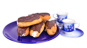 Eclairs on blue plate  with coffe cups Stock Image