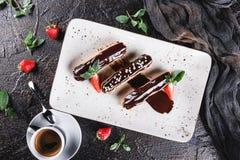 Eclairs caseiros ou profiteroles do bolo com creme, chocolate e morangos no fundo escuro servido com x?cara de caf? imagens de stock