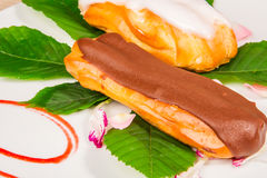 Eclairs with chocolate and vanilla icing Stock Images