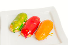 Eclairs with colorful caramel glaze Royalty Free Stock Photo