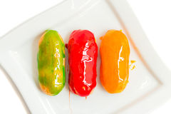 Eclairs with colorful caramel glaze on white plate Stock Images
