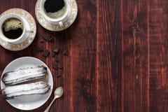 Eclairs de chocolate em um fundo de madeira imagem de stock royalty free