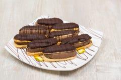 Eclairs de chocolate en la placa Fotos de archivo