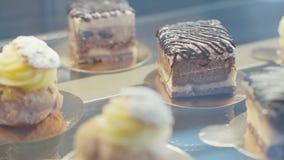 Eclairs del primer y tortas de chocolate en la vitrina de cristal metrajes