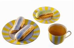 Eclairs deliciosos y una taza de té Fotografía de archivo