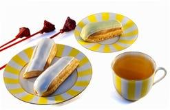 Eclairs deliciosos y una taza de té Fotografía de archivo libre de regalías