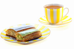 Eclairs deliciosos y una taza de té Imagen de archivo