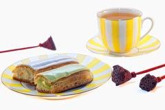 Eclairs deliciosos y una taza de té Imagenes de archivo