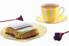 Eclairs deliciosos y una taza de té Fotos de archivo libres de regalías