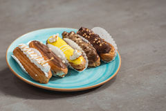 Eclairs with different ganache and icing with different toppings Royalty Free Stock Photography