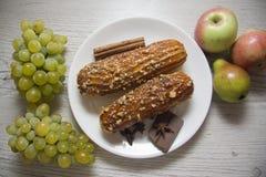 Eclairs e uvas Fotos de Stock