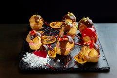 Eclairs franceses tradicionais com chocolate e porcas fotos de stock royalty free
