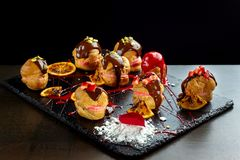 Eclairs franceses tradicionais com chocolate e porcas fotos de stock