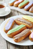 Eclairs with glaze. On a grey wooden table stock photography