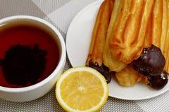 Eclairs i filiżanka herbata na białym tle zdjęcia stock