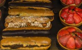 Eclairs med mandlar och choklad och efterrätt med jordgubbar Arkivbilder