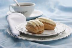 Eclairs mit Tee lizenzfreie stockbilder