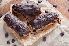 Eclairs o Profiterole con cioccolato fondente Cucinando sul cuocere SH Fotografia Stock Libera da Diritti